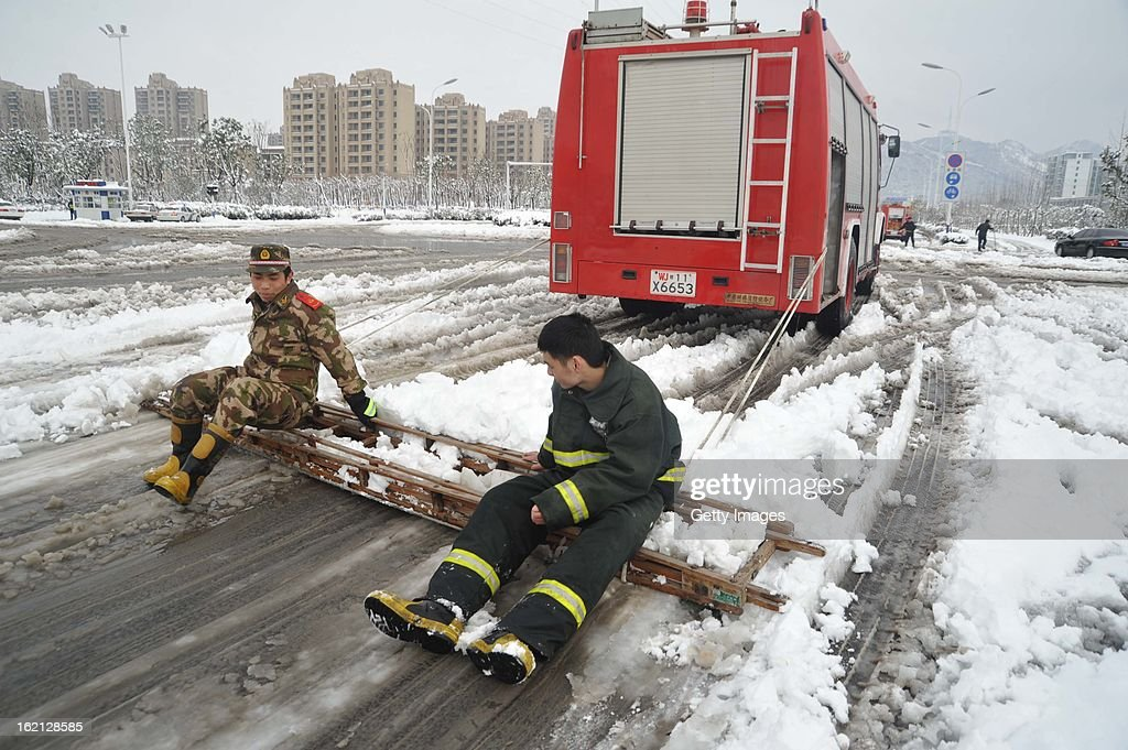 Firefighters clean a snow-covered road with a ladder on February 19, 2013 in Hefei, China. Heavy snow hit large areas of east China on Tuesday.