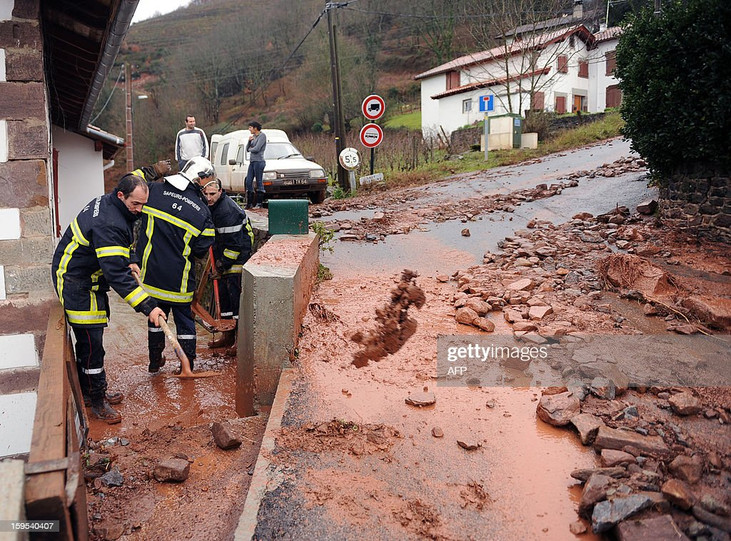Firefighters clean up a street after a mudslide following heavy rains in Ispoure, southeastern France, on January 15, 2013. AFP PHOTO / GAIZKA IROZ