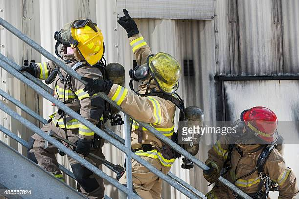 Firefighters climbing stairs outside industrial building