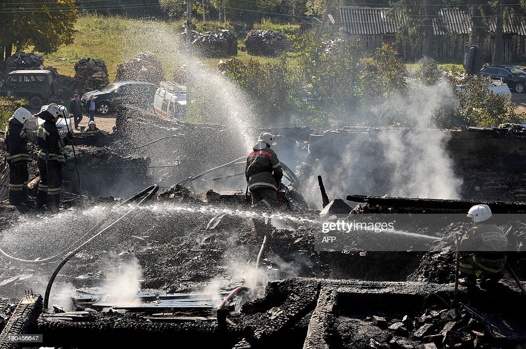 Firefighters continue to extinguish fire in the charring remains of a burned out psychiatric hospital in the village of Luka in the northwest Russian Novgorod region on September 13, 2013. Thirty seven people were killed when a fire swept through a wooden psychiatric hospital in northwest Russia overnight yesterday, regional investigators said. AFP PHOTO / OLGA MALTSEVA