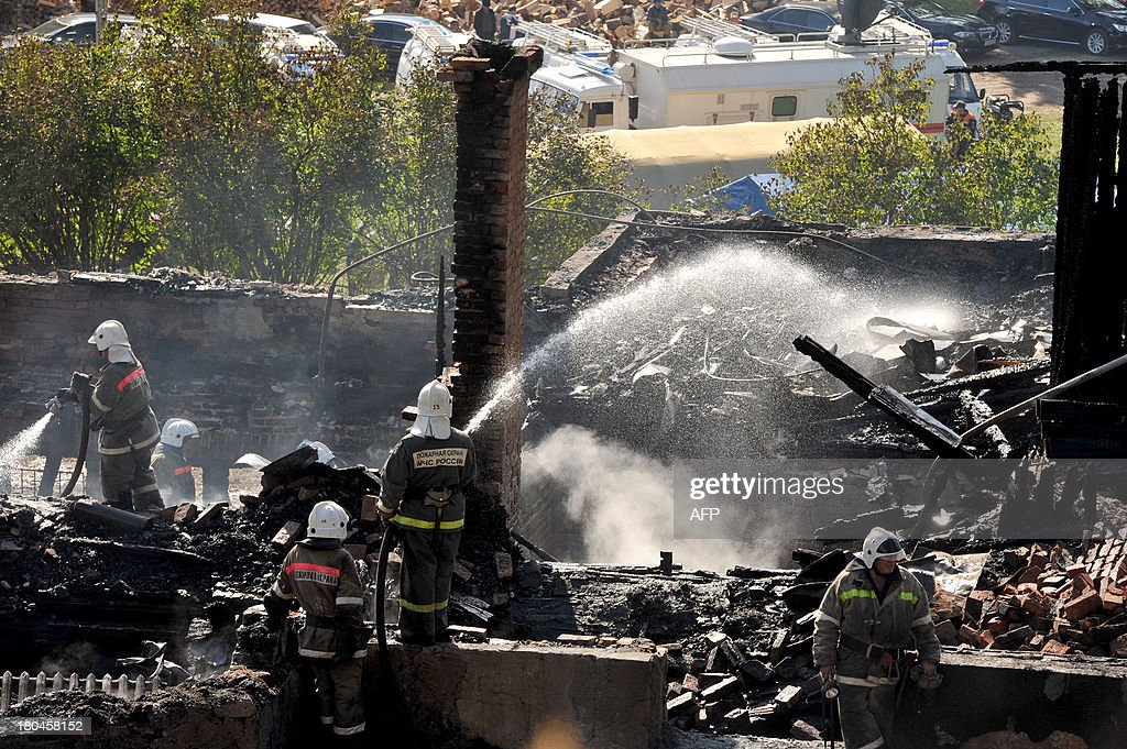 Firefighters continue to extinguish fire in the charring remains of a burned out psychiatric hospital in the village of Luka in the northwest Russian Novgorod region on September 13, 2013. Thirty seven people were killed when a fire swept through a wooden psychiatric hospital in northwest Russia overnight yesterday, regional investigators said.
