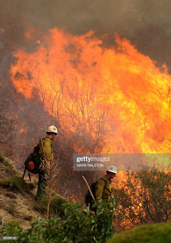 Firefighters control a fire burning behind houses in the suburb of Glendale on the outskirts of Los Angeles city on September 1 2009 A deadly...