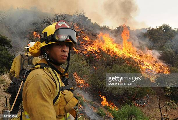 Firefighters control a fire next to houses in the suburb of Glendale on the outskirts of Los Angeles city on September 1 2009 A deadly wildfire...