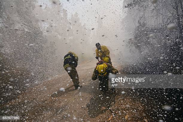 Firefighters cover themselves from the foam thrown by the super tanker Boeing 747400 firefighting plane in the effort to put out a forest fire in...