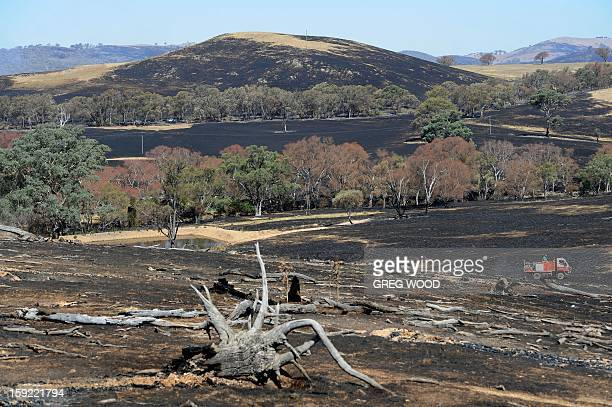 Firefighters cross a paddock blackened by recent bushfires near Bookham a small village in the Yass Shire in the southern region of Australia's New...