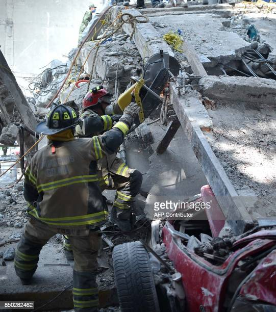 Firefighters cut concrete steel bars to clear the rubble on the site where a multistory building was flattened by a 71magnitude quake on the eve...
