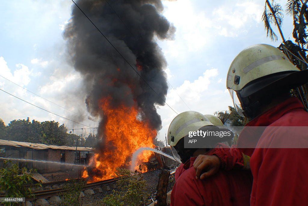 Firefighters (R) direct hose water towards a fire following a collision between a commuter train and fuel truck at Bintaro, western Jakarta, on December 9, 2013. At least four people were killed when a commuter train collided with a fuel truck near the Indonesian capital Jakarta on December 9, derailing a women-only carriage which burst into flames, officials said. AFP PHOTO / Bima SAKTI