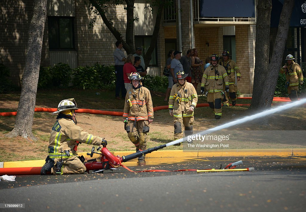 A firefighters directs water from a parking lot in an adjacent apartment complex as colleagues from throughout the region battle a huge blaze in a warehouse on S. Pickett street on September, 02, 2013 in Alexandria, VA.
