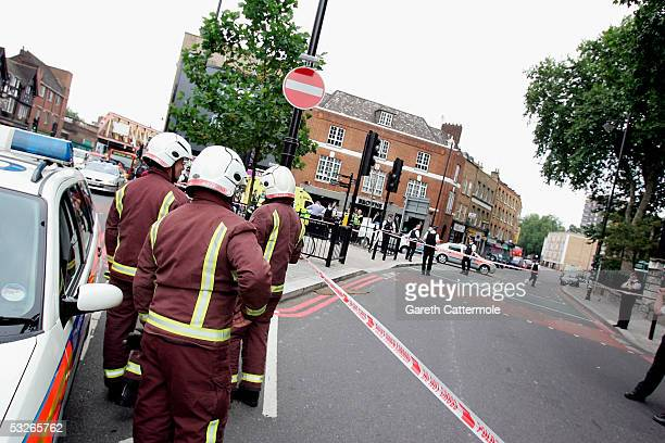 Firefighters discuss strategy on the closed Hackney Road in Bethnal Green on July 21 2005 in London England The windows of a number 26 travelling on...