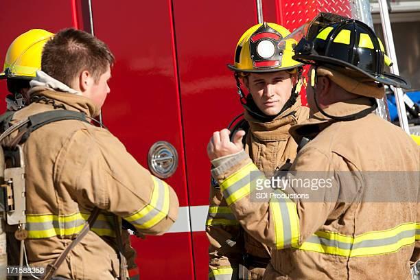 Feuerwehrleute über betrieblicher Verfahren vor Feuerwehrwagen