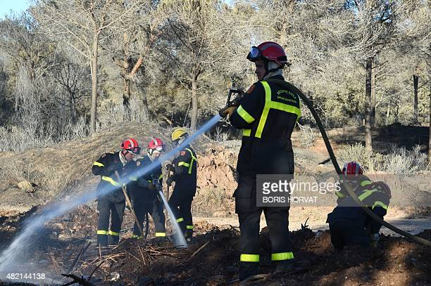 Firefighters douse an area near a campsite following a wildfire in BagnolsenForet in the Var department in southern France on July 27 2015 Three...
