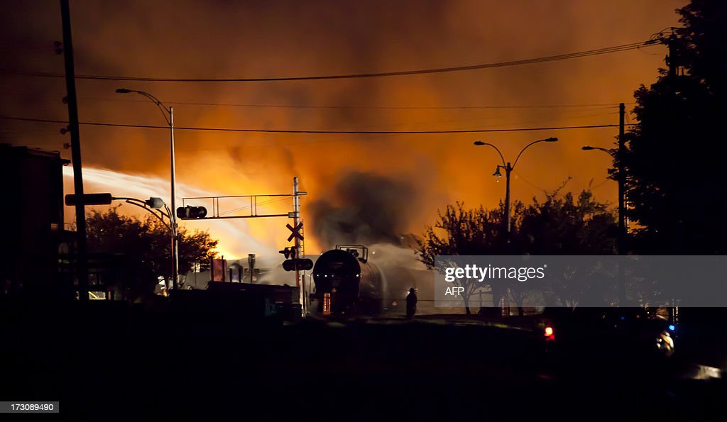 Firefighters douse blazes after a freight train loaded with oil derailed in LacMegantic in Canada's Quebec province on July 6 sparking explosions...