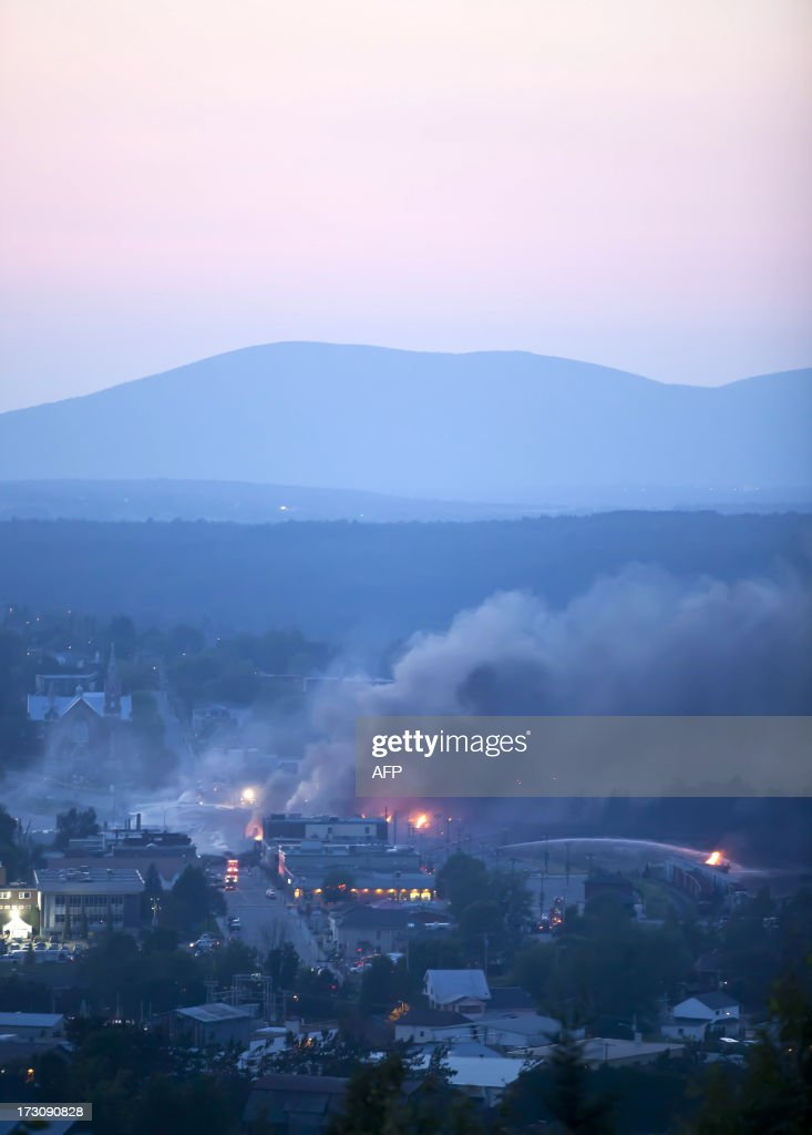 Firefighters douse blazes after a freight train loaded with oil derailed in Lac-Megantic in Canada's Quebec province on July 6, 2013, sparking explosions that engulfed about 30 buildings in fire. At least 80 people are missing after a driverless oil tanker train derailed and exploded in the small Canadian town of Lac-Megantic, destroying dozens of buildings, a firefighter back from the scene told AFP. AFP PHOTO / François Laplante-Delagrave