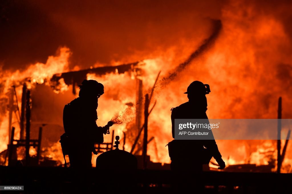 Firefighters douse flames as a home burns in the Napa wine region in California on October 9, 2017, as multiple wind-driven fires continue to whip through the region. /