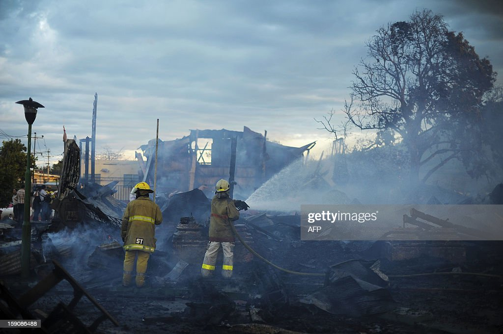Firefighters douse smouldering rubble following a blaze that destroyed the San Esteban Church, an historical landmark in downtown San Salvador, El Salvador on January 7, 2012. The San Esteban was built in the 19th century in Belgium, transported and assembled in one of the oldest localities of the capital city. AFP PHOTO/ Jose CABEZAS
