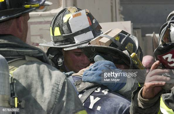 Firefighters embrace one another as they try to grapple with the terrorist attack on the World Trade Center on Sept 11 2001