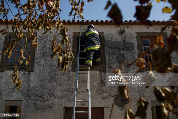 Firefighters enter to a burning house through a window to extinguish the fire in the village of Travanca do Mondego on October 17 2017 in Coimbra...