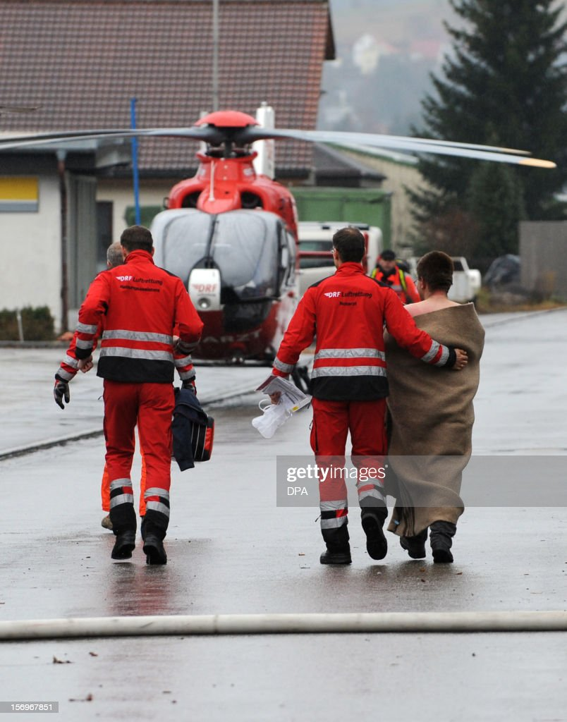 Firefighters escort an injured person at a workshop for handicapped people in Titisee- Neustadt, southern Germany on November 26, 2012. Fourteen people died after a fire broke out. AFP PHOTO / PATRICK SEEGER GERMANY OUT