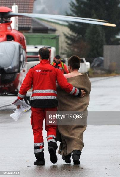 Firefighters escort an injured person at a workshop for handicapped people in Titisee Neustadt southern Germany on November 26 2012 Fourteen people...