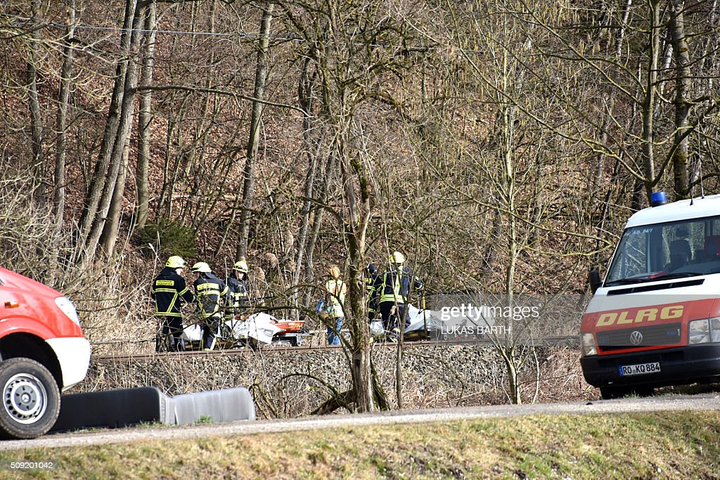 Firefighters evacuate bodies of victims at the site of a train accident near Bad Aibling, southern Germany, on February 9, 2016. Two commuter trains collided head-on near Bad Aibling, around 60 kilometres (40 miles) southeast of Munich, killing at least eight people and injuring around 100, in what is believed to be the country's first deadly rail accident in three years. / AFP / Lukas BARTH