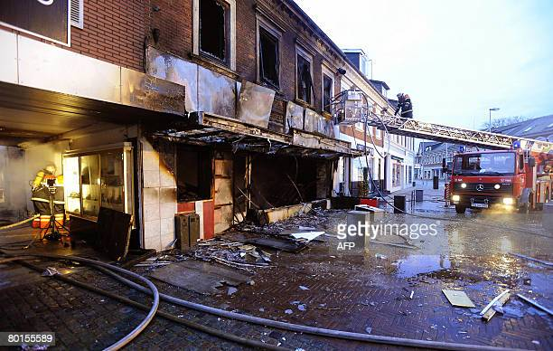 Firefighters extinguish a blaze at the Castello Pizza bar after an explosion early on March 7 2008 rocked the town of Bramming in Jutland A woman who...