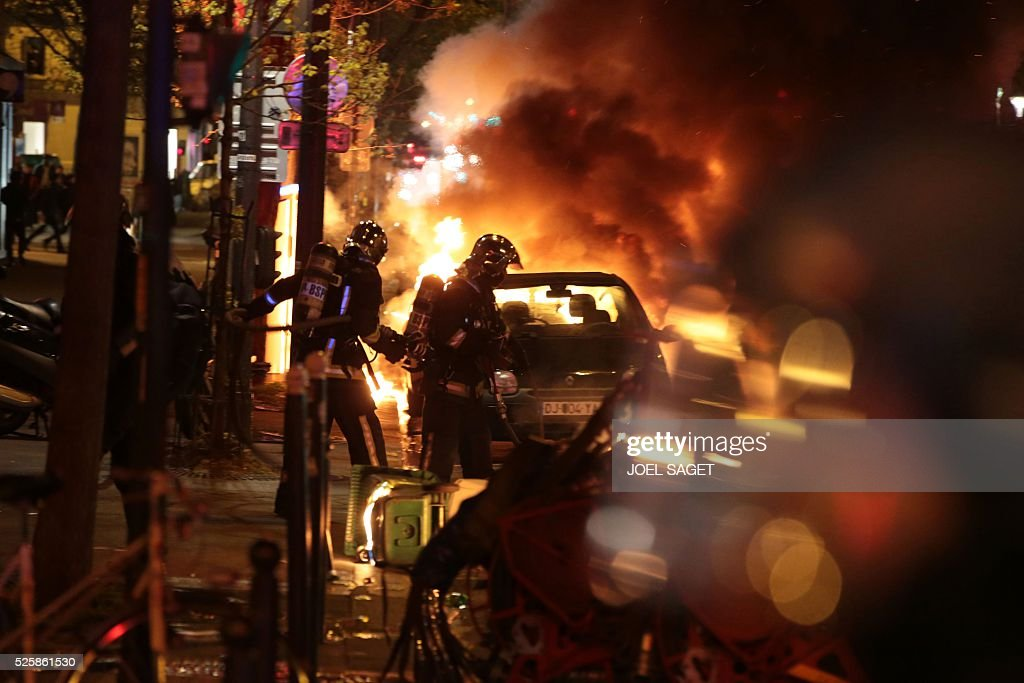 Firefighters extinguish a burning car as French Gendarmerie clear the Place de la Republique during a protest by the Nuit Debout, or 'Up All Night' movement who have been rallying against the French government's proposed labour reforms early on April 29, 2016. Twenty-seven people were arrested and 24 detained during the overnight clashes in the French capital as the police dispersed the protesters who began their began movement on March 31 in opposition to the government's proposed labour reforms.