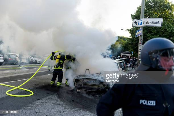 Firefighters extinguish a burning car in Hamburg Germany on July 6 2017 The police stopped the leftradical demonstration quotG20 Welcome to Hellquot...