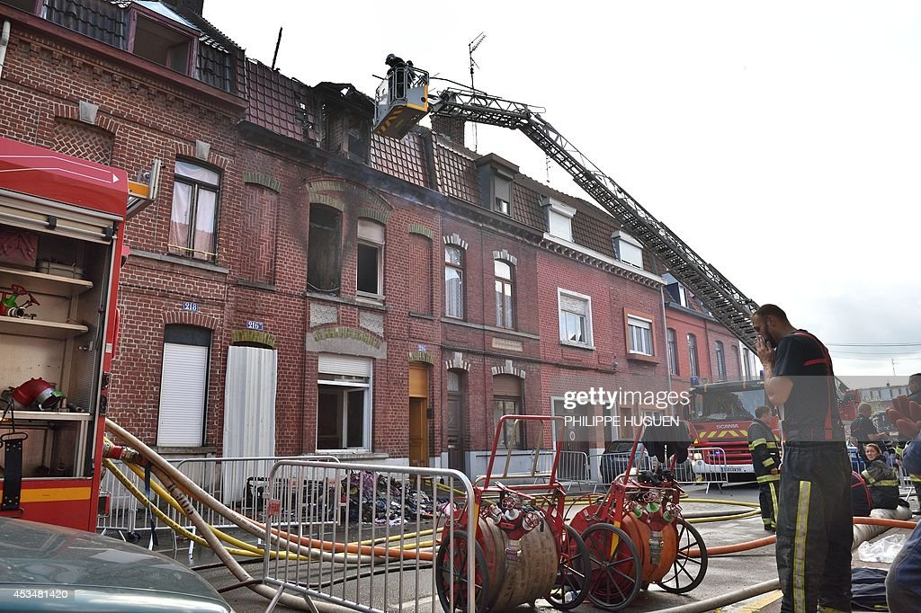 Firefighters extinguish a fire in a house in Roubaix, northern France, on August 11, 2014. A six-year-old child died and an adult and another child were seriously burned in the fire that started at 9am, the firefighters said.