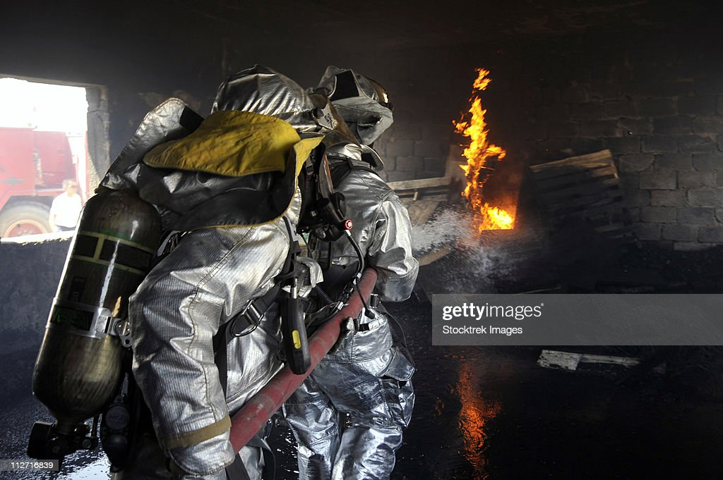 Firefighters extinguish a fire in a training room during live burn training.