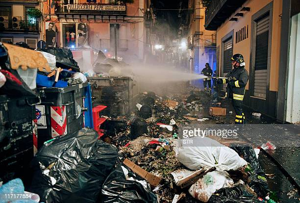 Firefighters extinguish a fire set in waste containers and rubbish left in the street overnight on June 24 2011 in Naples Firefighters in...