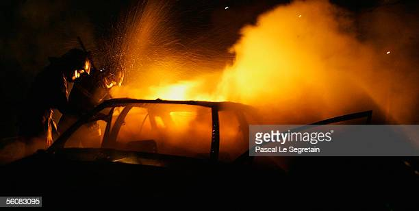 Firefighters extinguish a torched car on November 4 2005 in Le Blanc Mesnil outside Paris France Riots continue on the eighth consecutive night...