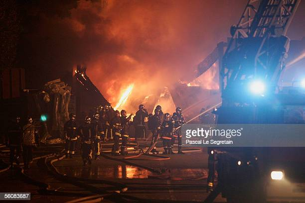 Firefighters extinguish a warehouse set ablaze in the early hours November 4 2005 in AulnaysousBois outside Paris France Riots continue on the eighth...