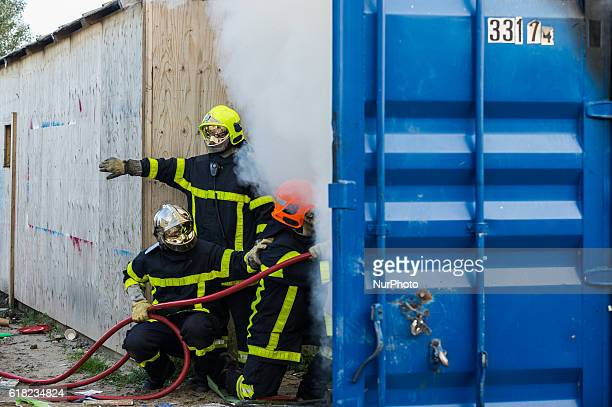 Firefighters extinguish during the eviction of the Calais Jungle a hut which was set on fire in Calais France on 25 October 2016 Up to the evening...