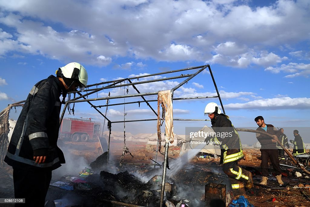 Firefighters extinguish fire after a Syrian regime warcraft targeted the Kamuna refugee camp near the Sarmada town of Idlib province, Syria on May 05, 2016. Eight people were killed and another 30 injured when a regime warcraft targeted the Kamuna refugee camp.