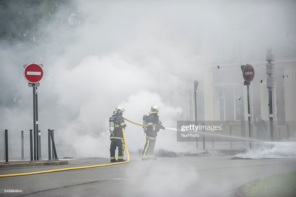 Firefighters extinguish the tire fire around the roundabout Post in Lille, France on june 28, 2016. A new national day of action against labor law takes place throughout France. Economic blocking action was planned by the CGT in Lille this morning at 6:30 am.