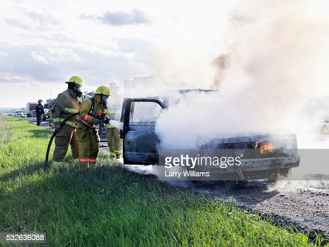 Firefighters Extinguishing An Suv On Fire Stock Photo Getty Images