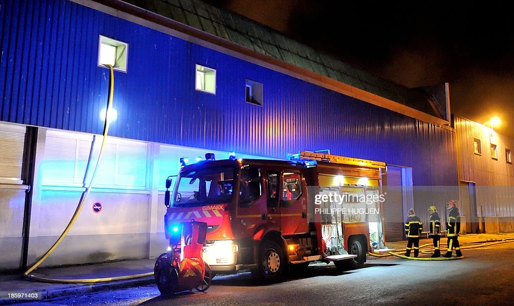 Firefighters fight against a fire in a warehouse containing potentially explosive material on October 27, 2013 in Boulogne-Sur-Mer, northern France.