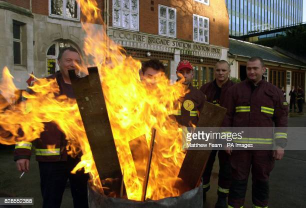 Firefighters from Blue and Green watches at Euston Fire Station in London stand in front of a brazier after coming out on strike at the start of...
