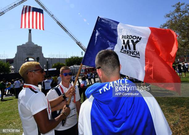 Firefighters from France show their flag before marching into the stadium during the opening ceremony of the World Police and Fire Games at the LA...