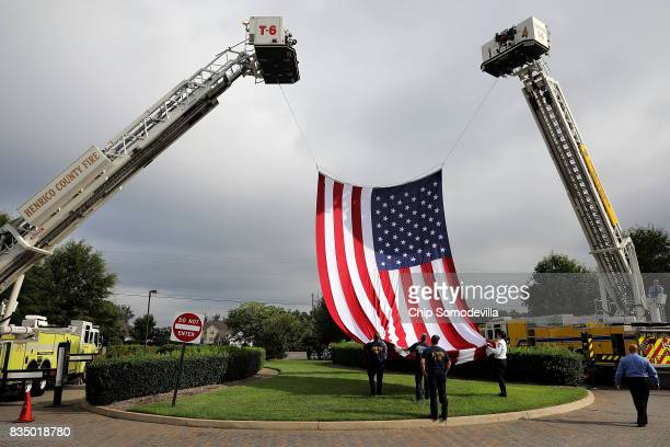Firefighters from Henrico and Chesterfield counties raise a large US flag in front of Saint PaulÕs Baptist Church ahead of the funeral for Virginia...