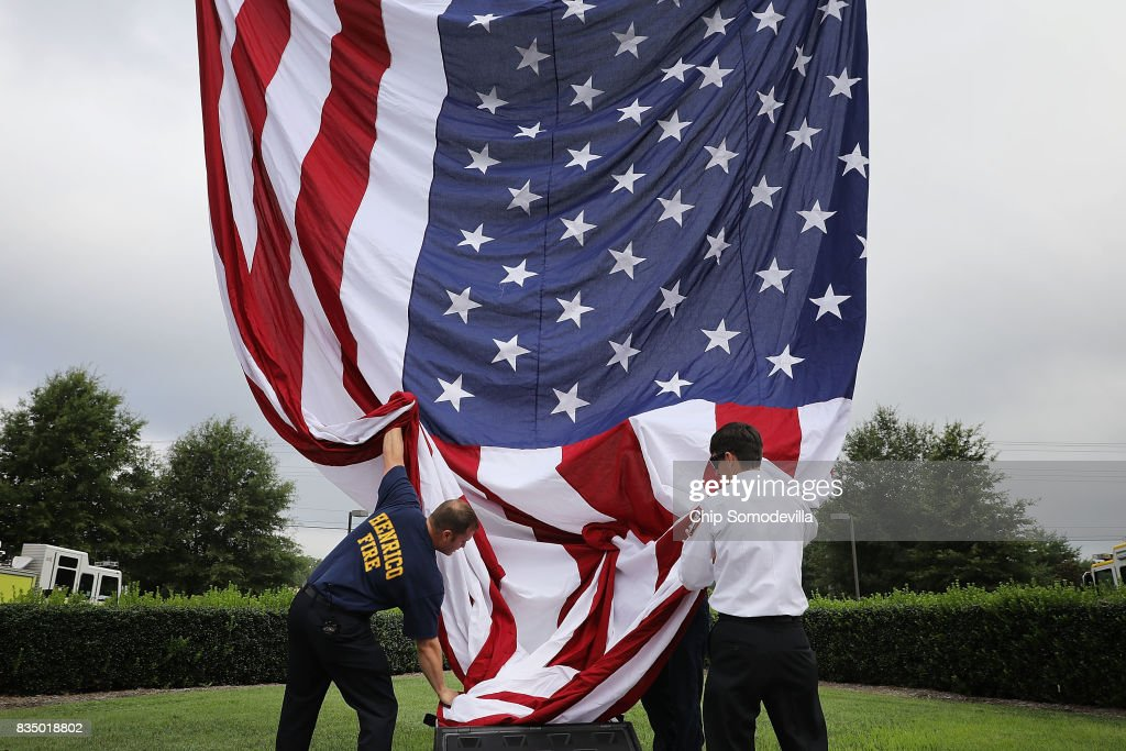 Firefighters from Henrico and Chesterfield counties raise a large U.S. flag in front of Saint Paul's Baptist Church ahead of the funeral for Virginia State Police Trooper Pilot Berke M.M. Bates August 18, 2017 in Richmond, Virginia. Bates and Lieutenant Pilot Jay Cullen were killed when their Bell 407 helicopter crashed into a wooded area while they were monitoring the civil unrest during the white supremacy 'Unite the Right' rally August 12 in Charlottesville, VA.