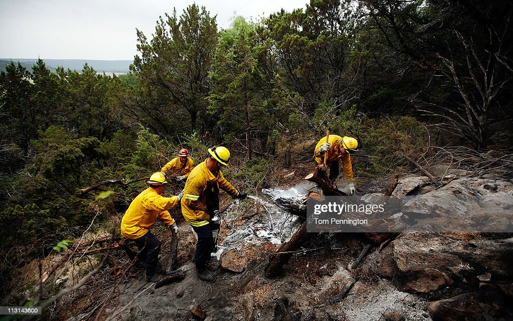 Firefighters from Lewisville and Coppell, Texas work to extinguish a hotspot fire in rugged terrain April 24, 2011 near Graford, Texas. Cooler tempratures and high humidity has helped firefighters contain the PK Complex Fire that has destroyed more than 160 homes in the area.