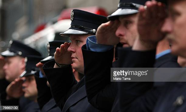 Firefighters from Manhattan's Engine 7 Ladder 1 salute during a moment of silence marking the World Trade Center attacks September 11 2007 in New...