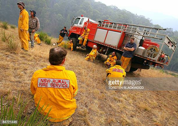 Firefighters from New South Wales rest after battling a bushfire in the Kiewa Valley threatening the town of Dederang in the Victoria Alps on...