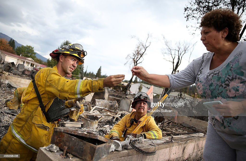 Firefighters from Redding California help a resident search for personal belongings in the remains of her destroyed home on September 16 2014 in Weed...