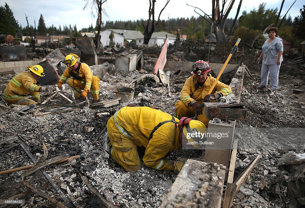 Firefighters from Redding California help a resident serach for personal belongings in the remains of her destroyed home on September 16 2014 in Weed...