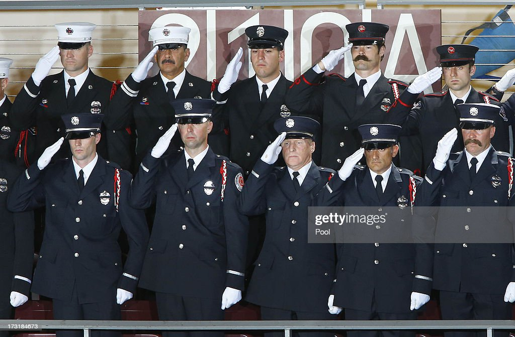 Firefighters from Sacramento stand during the national anthem during a memorial service honoring 19 fallen firefighters at Tim's Toyota Center July 9, 2013 in Prescott Valley, Arizona. The 19 firefighters, of the Granite Mountain Hotshots crew, died battling the fast-moving wildfire on June 30.