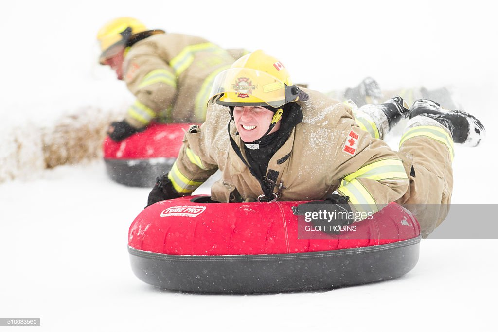 Firefighters from St. Thomas compete at the World Tubing Championship in St. Thomas, Ontario, February 13, 2016. The inaugural event, a fundraiser for the Special Care Nursery at St. Thomas Elgin General Hospital attracted nearly 50 teams. / AFP / Geoff Robins