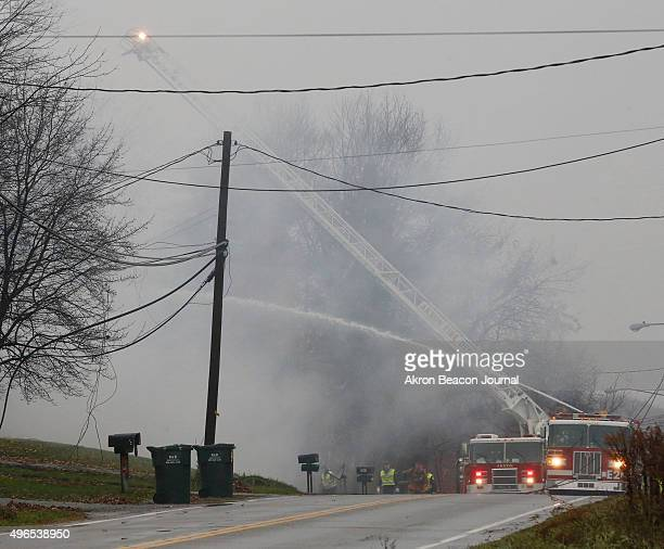 Firefighters from the Akron Fire Department work on the fire caused by a small passenger jet crashing into a home on Mogadore Road on Tuesday Nov 10...
