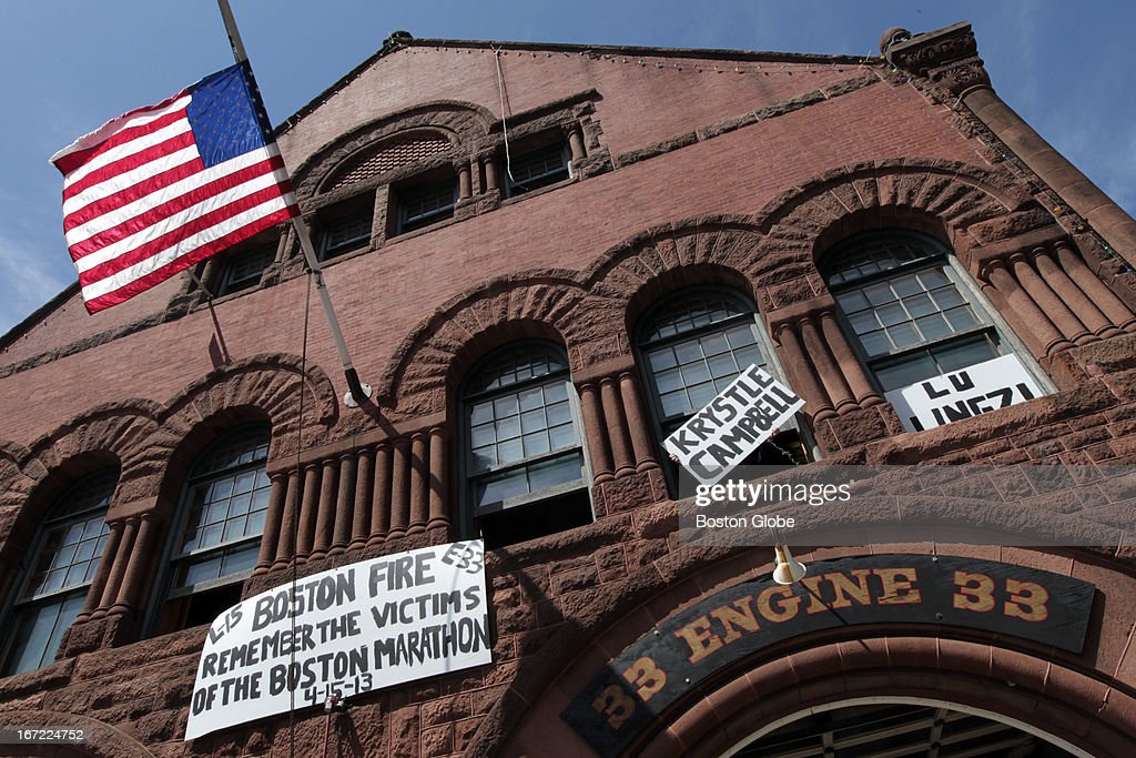 Firefighters from the Boylston Street Firehouse, Engine 33 Ladder 15 hang signs they painted in honor of the victims at the firehouse before the moment of silence today at 2:50 p.m. A moment of silence was held at 2:50 p.m. for the victims of the Boston Marathon bombings which occurred one week ago today.